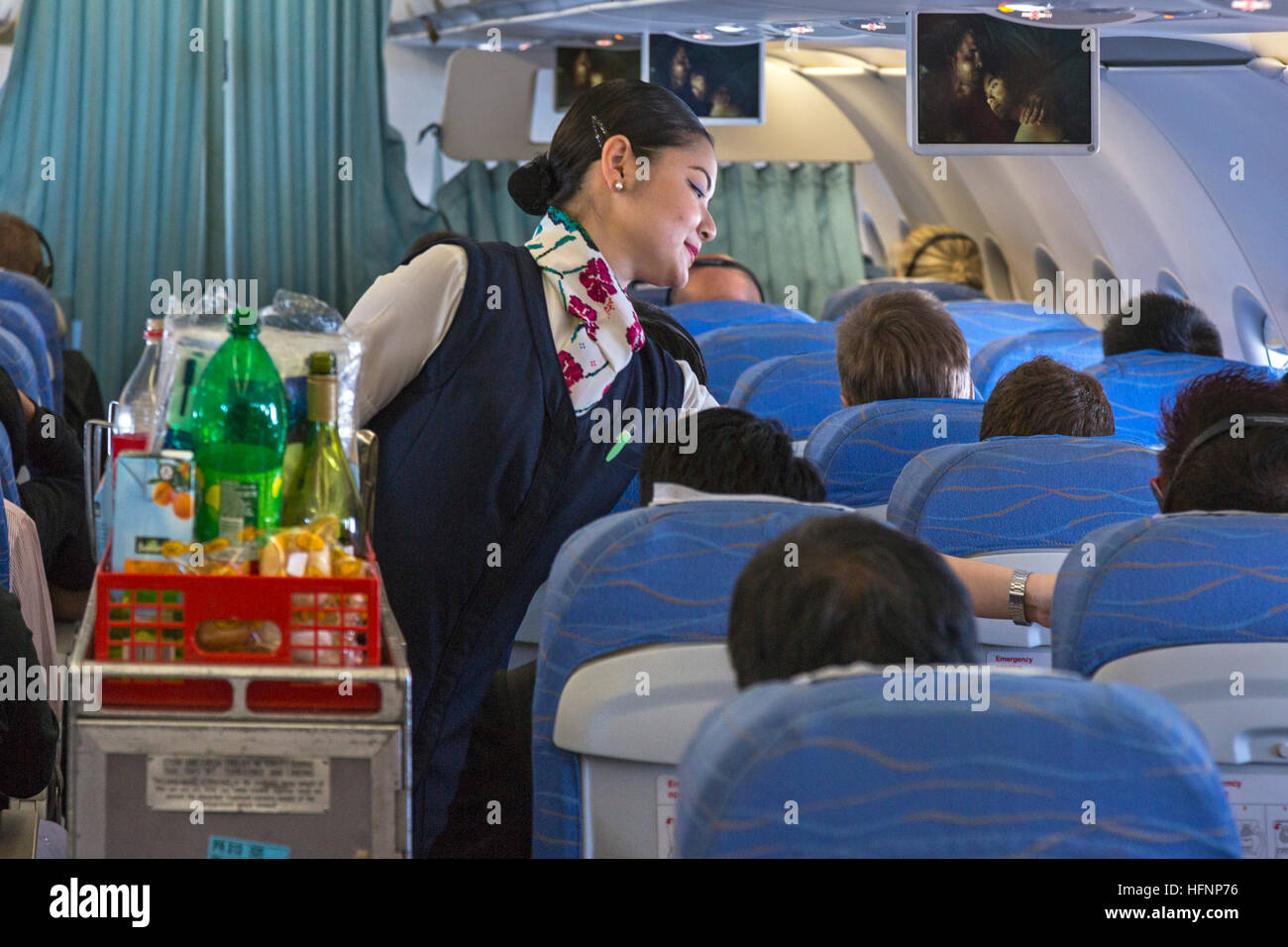Cabin crew and passengers on Philippine Airlines flight from Manila - Stock Image