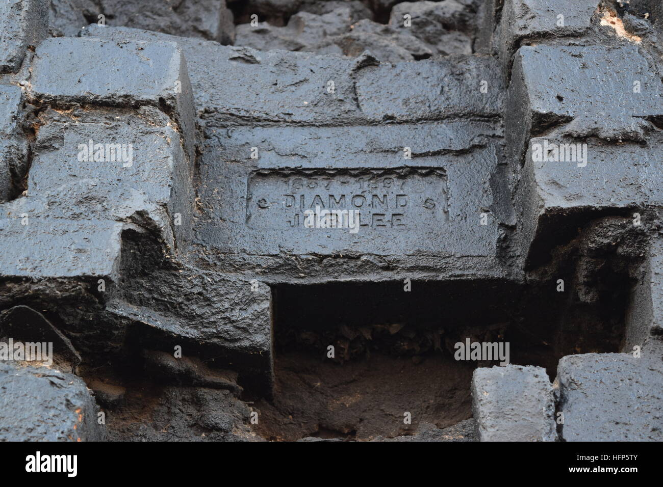 A Victorian Diamond Jubilee Brick on a ruined fireplace in the Gun Quarter Birmingham - Stock Image