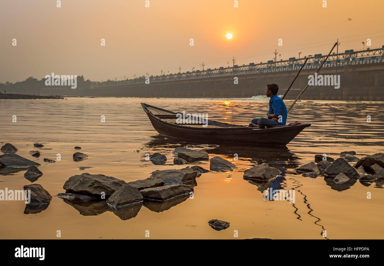 An oarsman sits on his boat at sunset on river Damodar near the Durgapur Barrage, West Bengal, India. Stock Photo