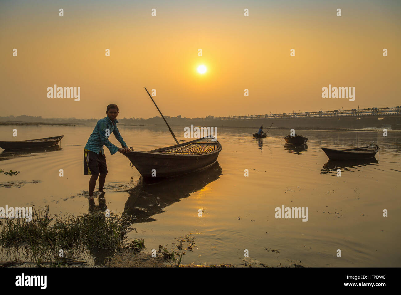 Oarsman tries to tow his boat to shore at sunset on river Damodar near the Durgapur Barrage, West Bengal, India. Stock Photo