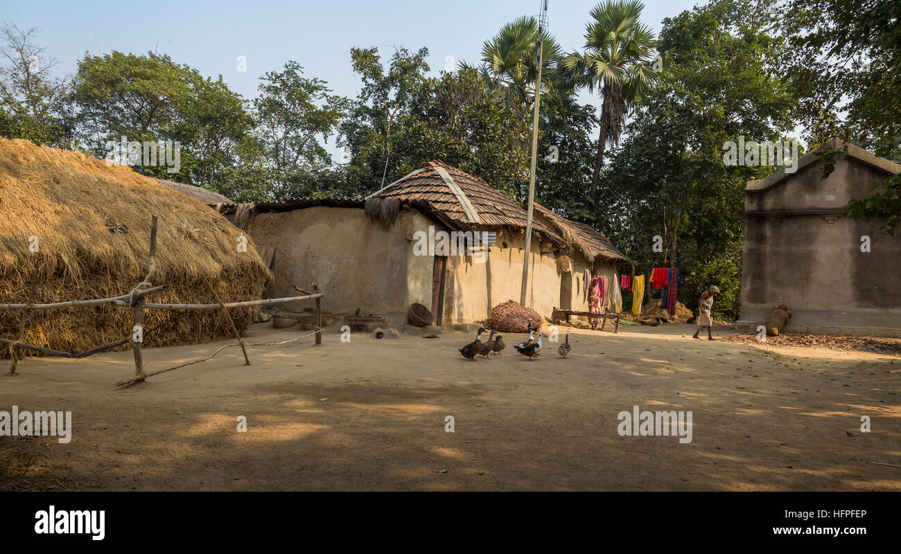 Rural Indian Village In Bankura West Bengal With Mud Huts Poultry And Old Tribal Women Standing On The Courtyard