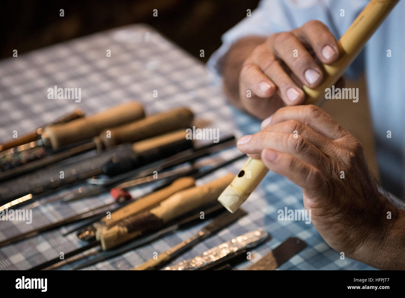 Senior man  crafting and playing a handmade cyprus traditional music instrument called flogera. - Stock Image