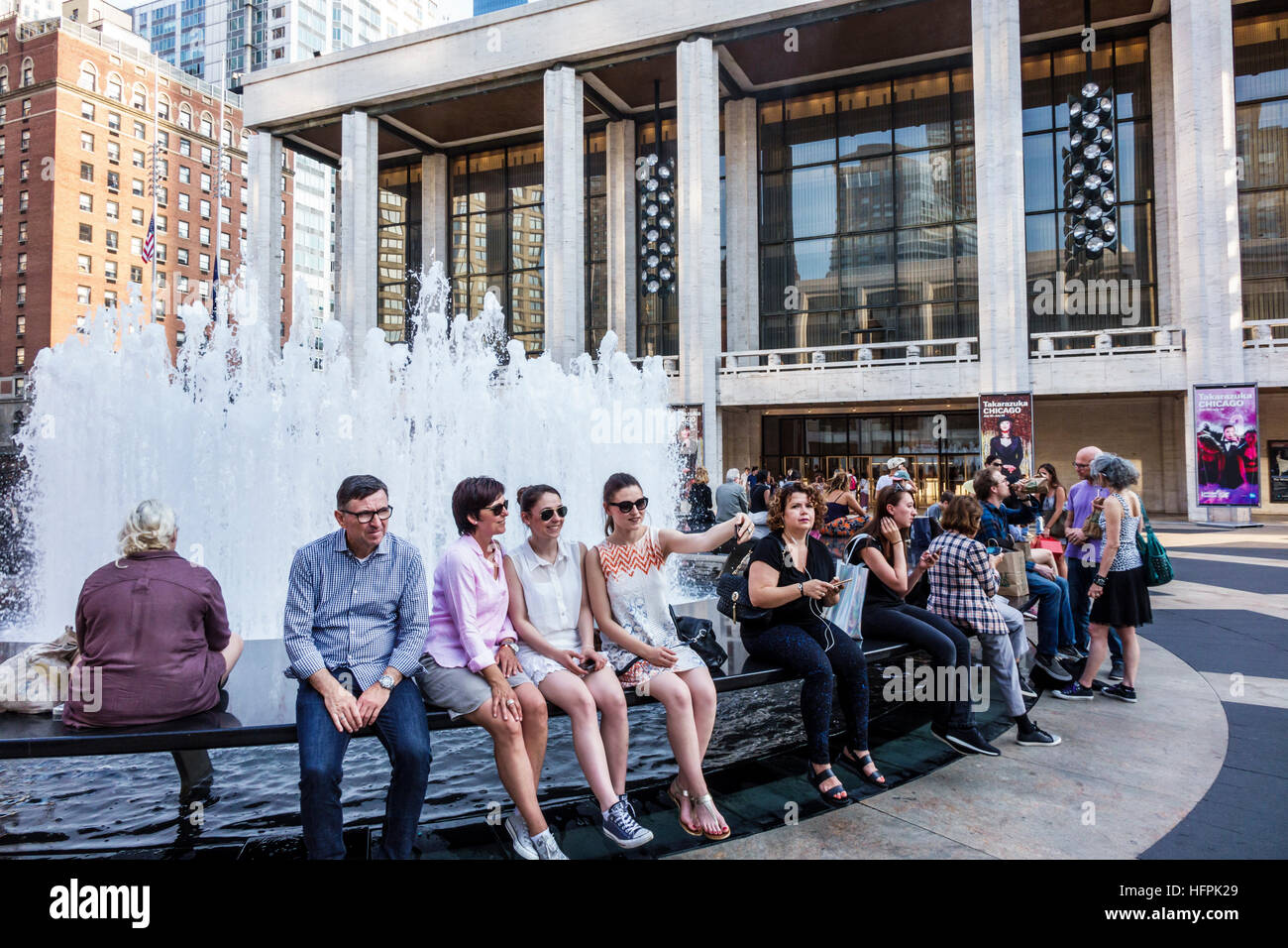 Manhattan New York City NYC NY Lincoln Square Lincoln Center Plaza PAC fountain man woman sitting selfie fountain - Stock Image