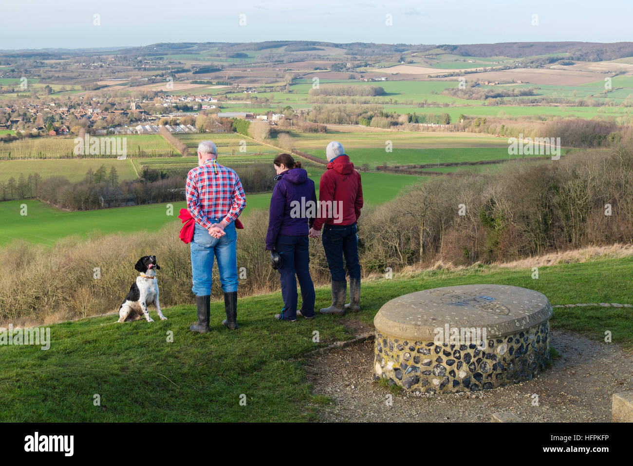 People looking at view with a dog by Wye Crown Millennium stone in Wye National Nature Reserve on North Downs Way. - Stock Image
