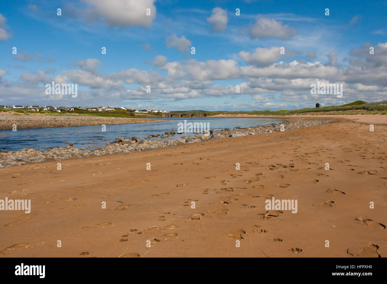 Sandy beach with rocks on the west coast of Ireland with a small river running into the Atlantic ocean at low tide. - Stock Image