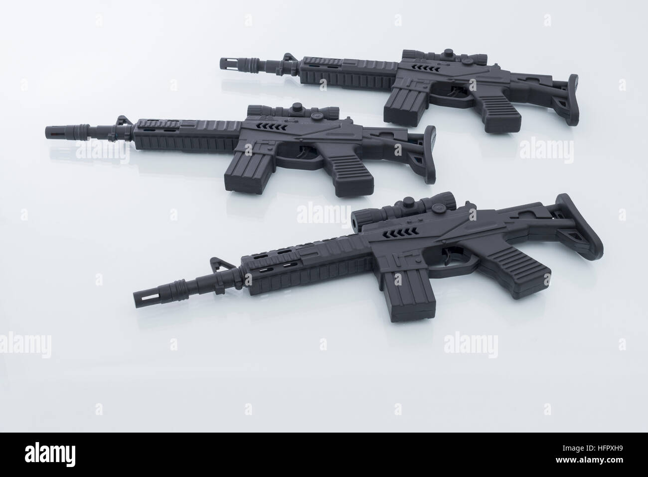Black toy assault rifles - as visual metaphor for concept of gun violence, gun crime, US gun laws, drugs crime and - Stock Image