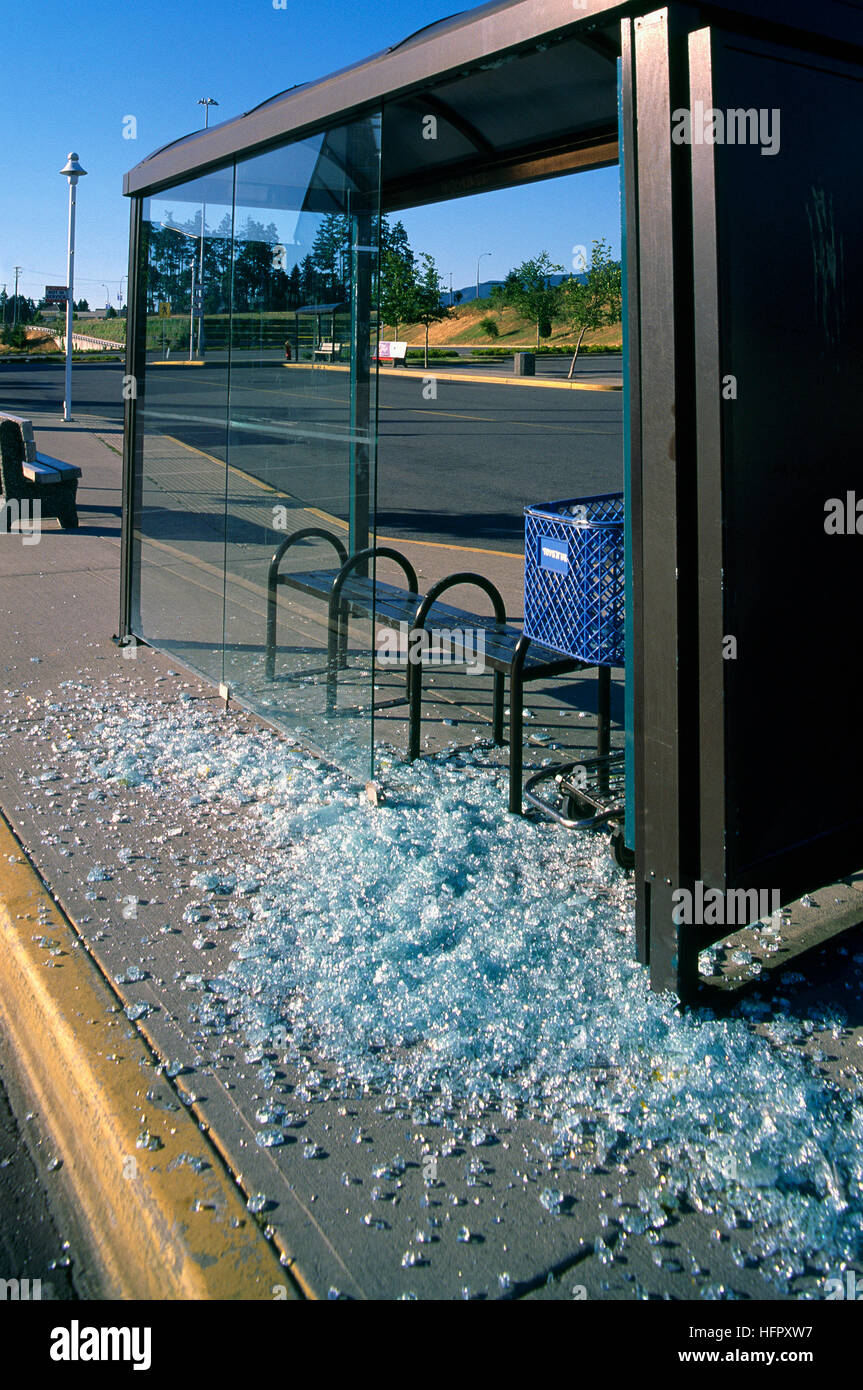 Vandalism at Bus Stop, Vandalized Bus Shelter - Broken Glass Shards on Pavement - Stock Image