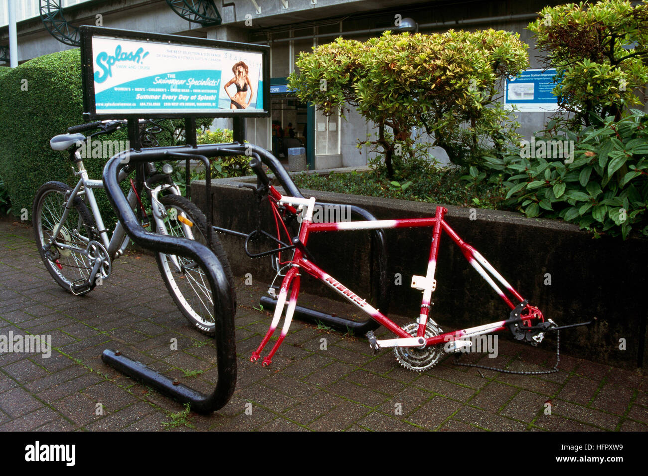 Vandalism - Vandalized Bicycle locked to Bike Stand, Frame remains after Wheels and Seat stolen - Stock Image