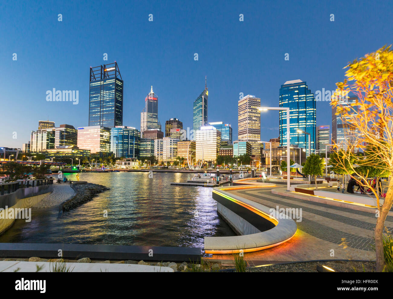 The waterfront precinct of Elizabeth Quay illuminated at twilght with the city skyline beyond, Perth, Western Australia, - Stock Image