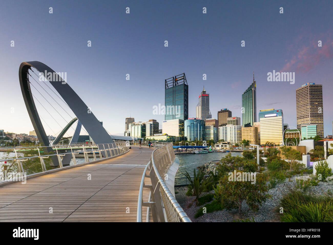 Twilight view along the Elizabeth Quay pedestrian bridge to the city skyline beyond, Perth, Western Australia, Australia - Stock Image