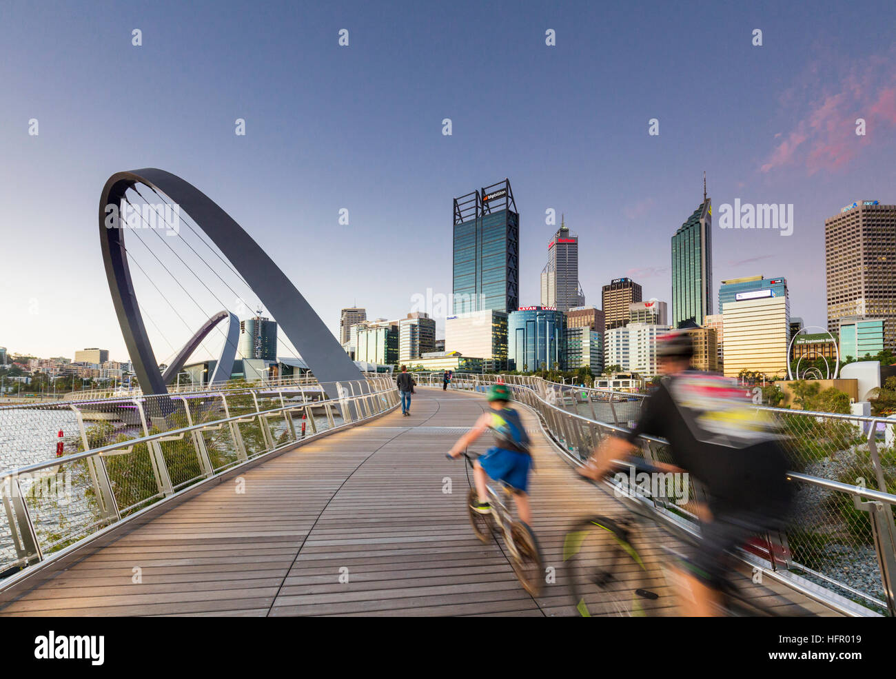 Cyclists crossing the Elizabeth Quay bridge at twilight with the city skyline beyond, Perth, Western Australia, - Stock Image
