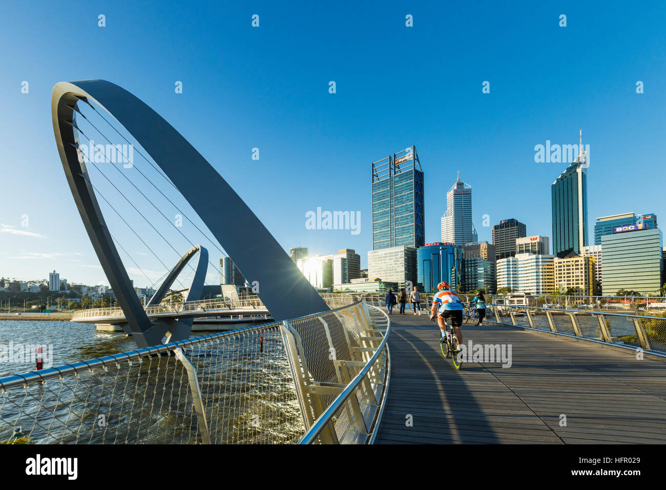 Cyclist crossing the Elizabeth Quay pedestrian bridge with the city skyline beyond, Perth, Western Australia, Australia Stock Photo