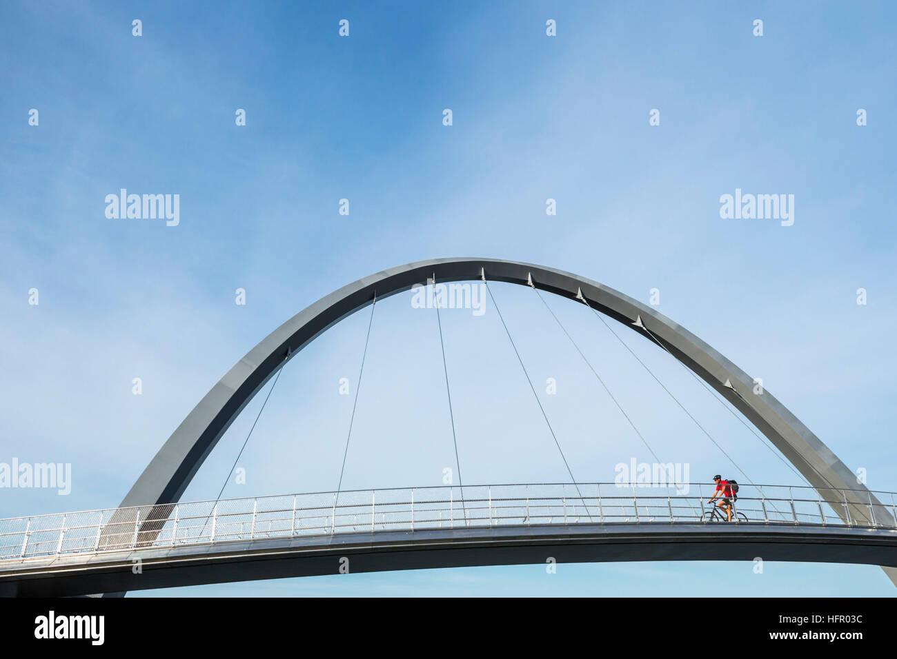 Cyclist crossing the Elizabeth Quay bridge on the Swan River, Perth, Western Australia, Australia - Stock Image