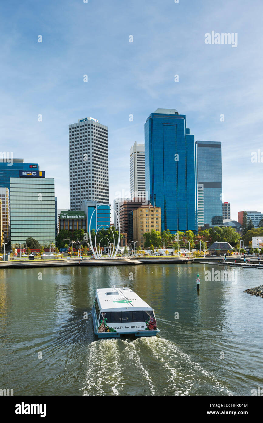 A Swan River ferry arriving at Elizabeth Quay ferry terminal with the city skyline beyond.  Perth, Western Australia, - Stock Image