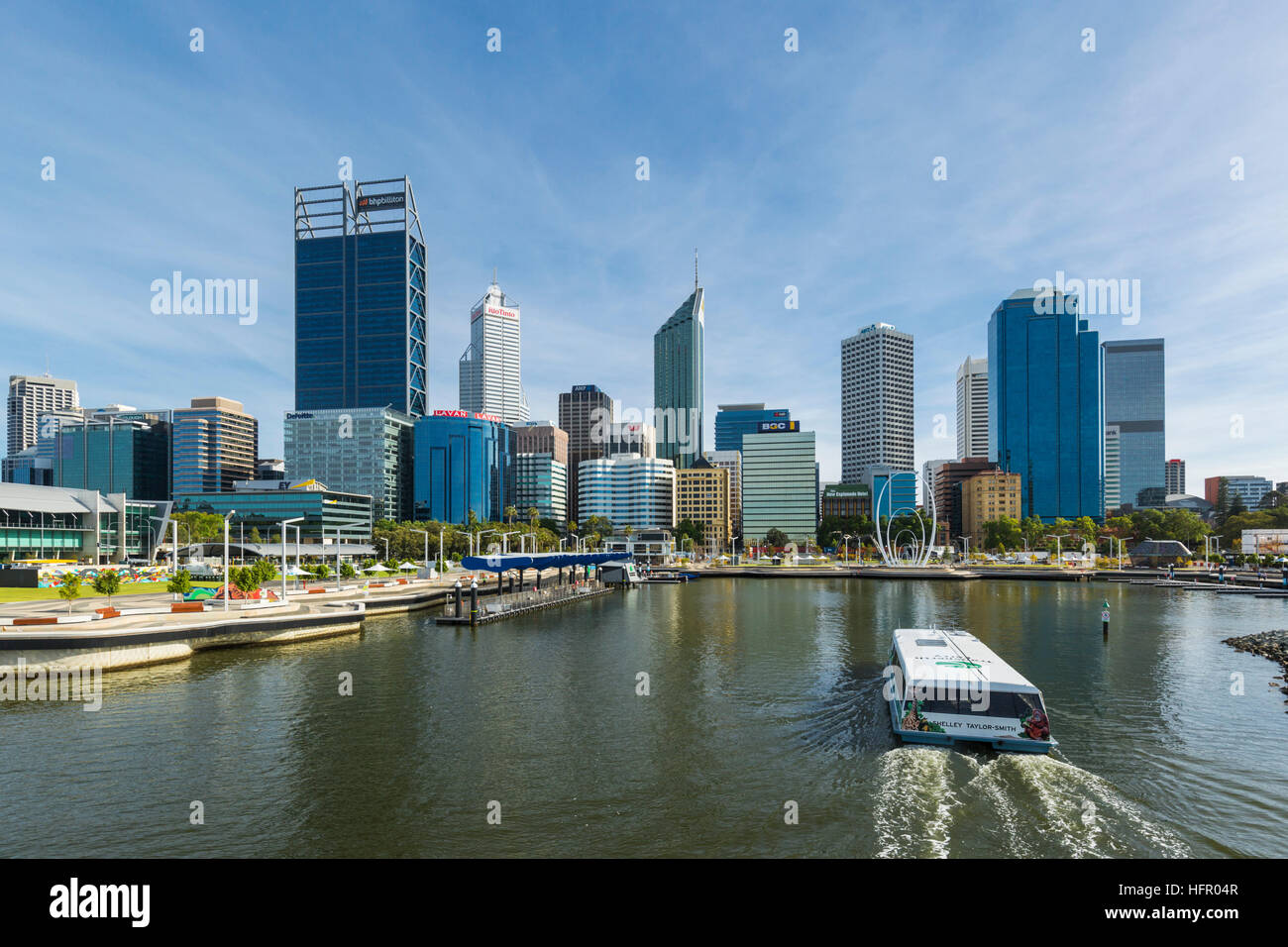 A Swan River ferry arriving at Elizabeth Quay ferry terminal with the city skyline beyond.  Perth, Western Australia, Stock Photo