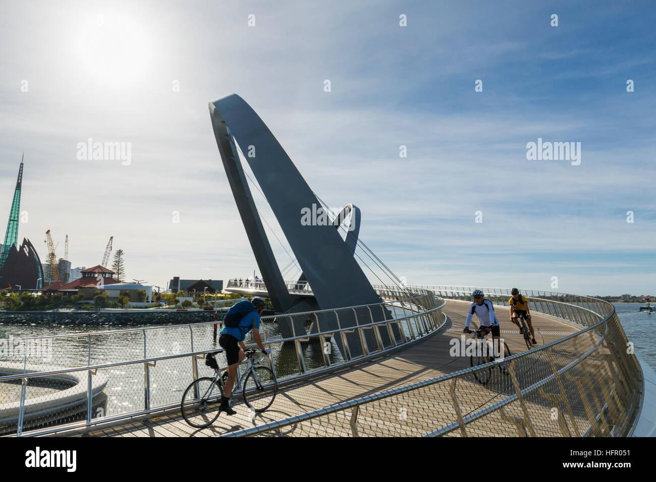 Early morning cyclists crossing the Elizabeth Quay pedestrian bridge, Perth, Western Australia, Australia - Stock Image