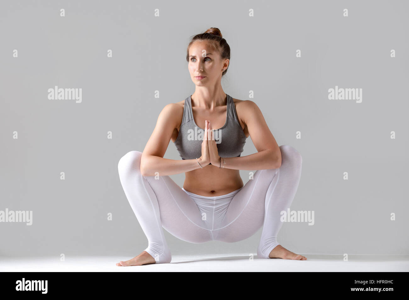 Young woman in Malasana pose, grey studio background - Stock Image