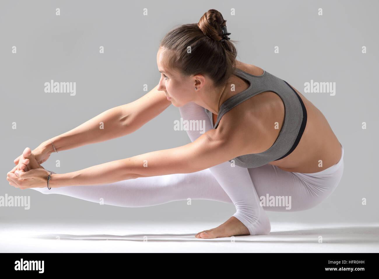 Woman doing Eka Pada Padangusthasana pose with squat - Stock Image