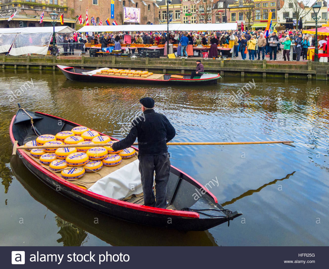 Netherlands, North Holland, Alkmaar. Man delivering yellow wheels of Dutch Cheese, Beemster, by boat to cheese market. - Stock Image