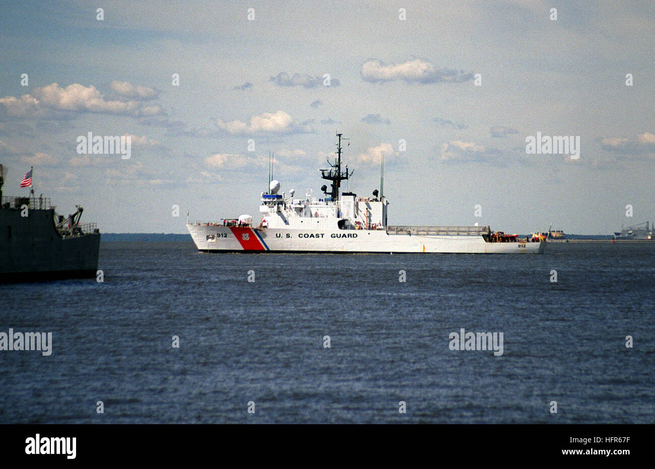 Port side view of the US Coast Guard Famous Class Medium-Endurance Cutter USCG LEGARE (WMEC 912) passing by pier - Stock Image
