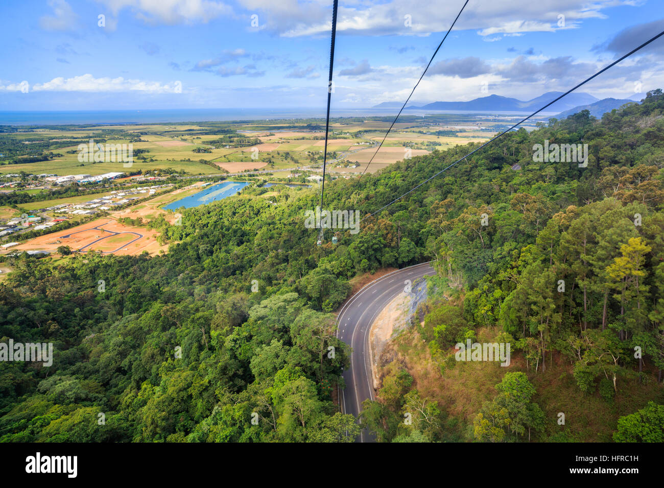 Kurana Skyrail Rainforest Cableway cable car going over a road  with the Cairns terminal in the distance. Queensland, - Stock Image