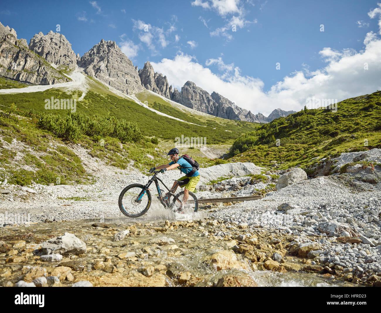 Mountainbiker rides with his mountain bike through a stream, in the background mountain chain Kalkkögel, Stubai - Stock Image