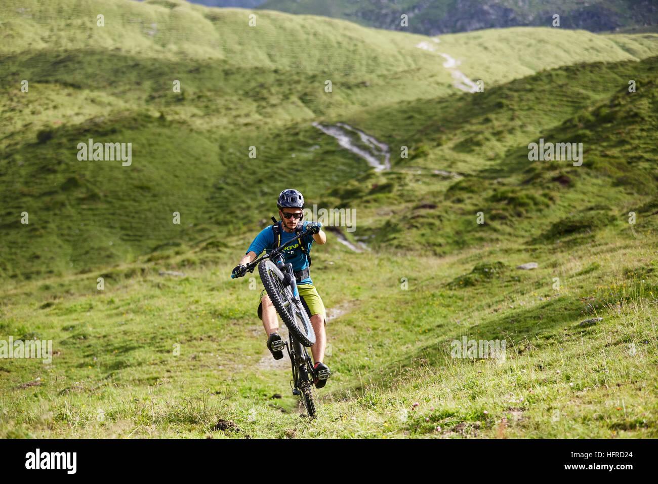 Mountain Biker rides a trail in the hilly landscape, Kalkkögel, Tyrol, Austria - Stock Image