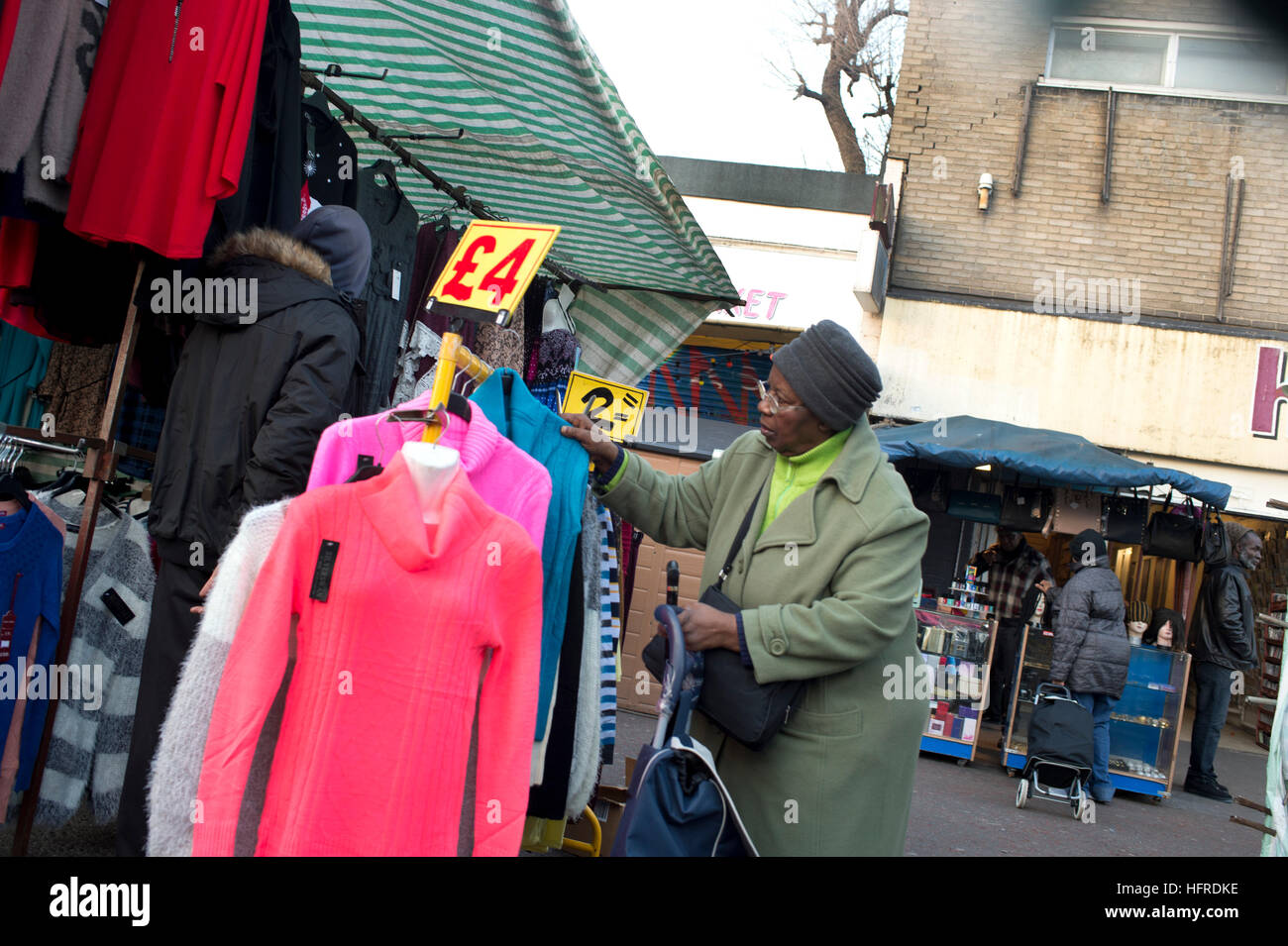 Hackney. Ridley Road market. An Afro Caribbean woman shopper examines the bargain clothes rack - Stock Image