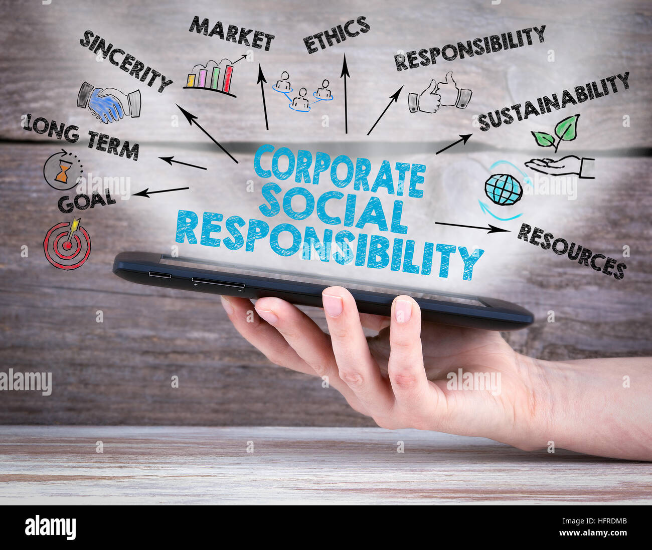 Corporate Social Responsibility Concept. Tablet computer in the hand. Old wooden background. - Stock Image