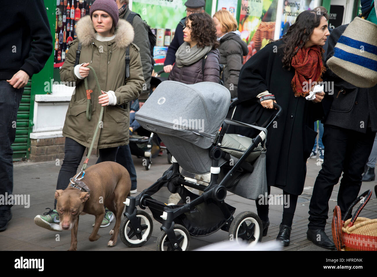 Hackney. Broadway market. Christmas shoppers with dog and pram - Stock Image