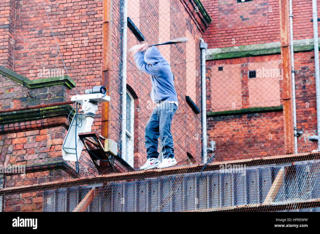 A republican youth uses a stick to break CCTV cameras on a security fence around a PSNI police station - Stock Image
