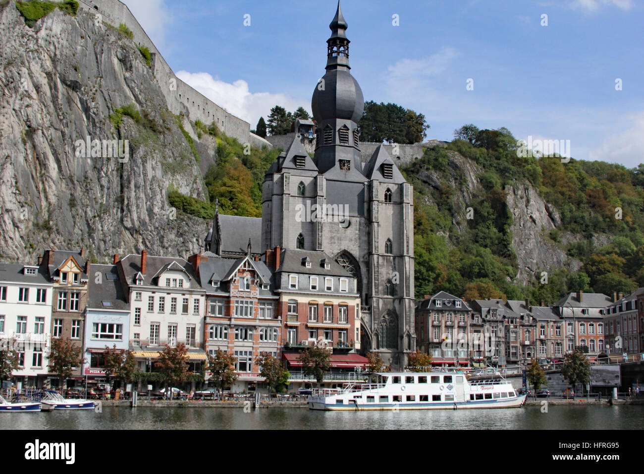 Church of Our Lady in Dinant Belgium towers over the city with cruise boats ply the Meuse River Stock Photo