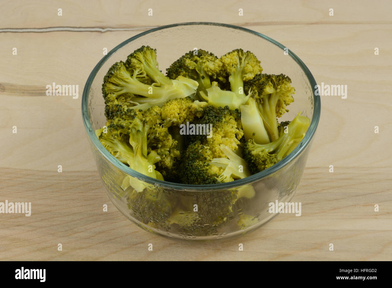 Steamed broccoli in glass bowl - Stock Image