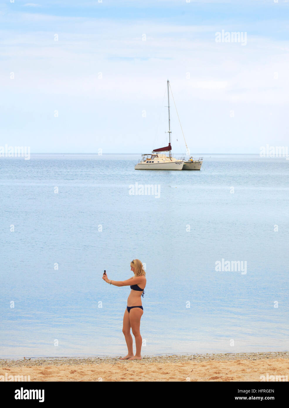 A girl in her early 20s taking a selfie on the beach with a catamaran yacht in the distance. - Stock Image