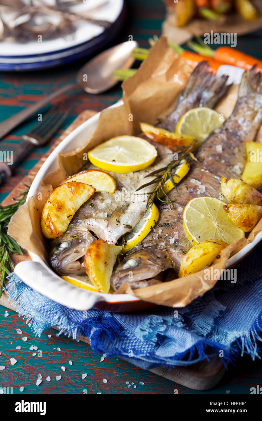 An oven roasted trout in a casserole on a rustic table. With carrots and potatoes on the side. Stock Photo