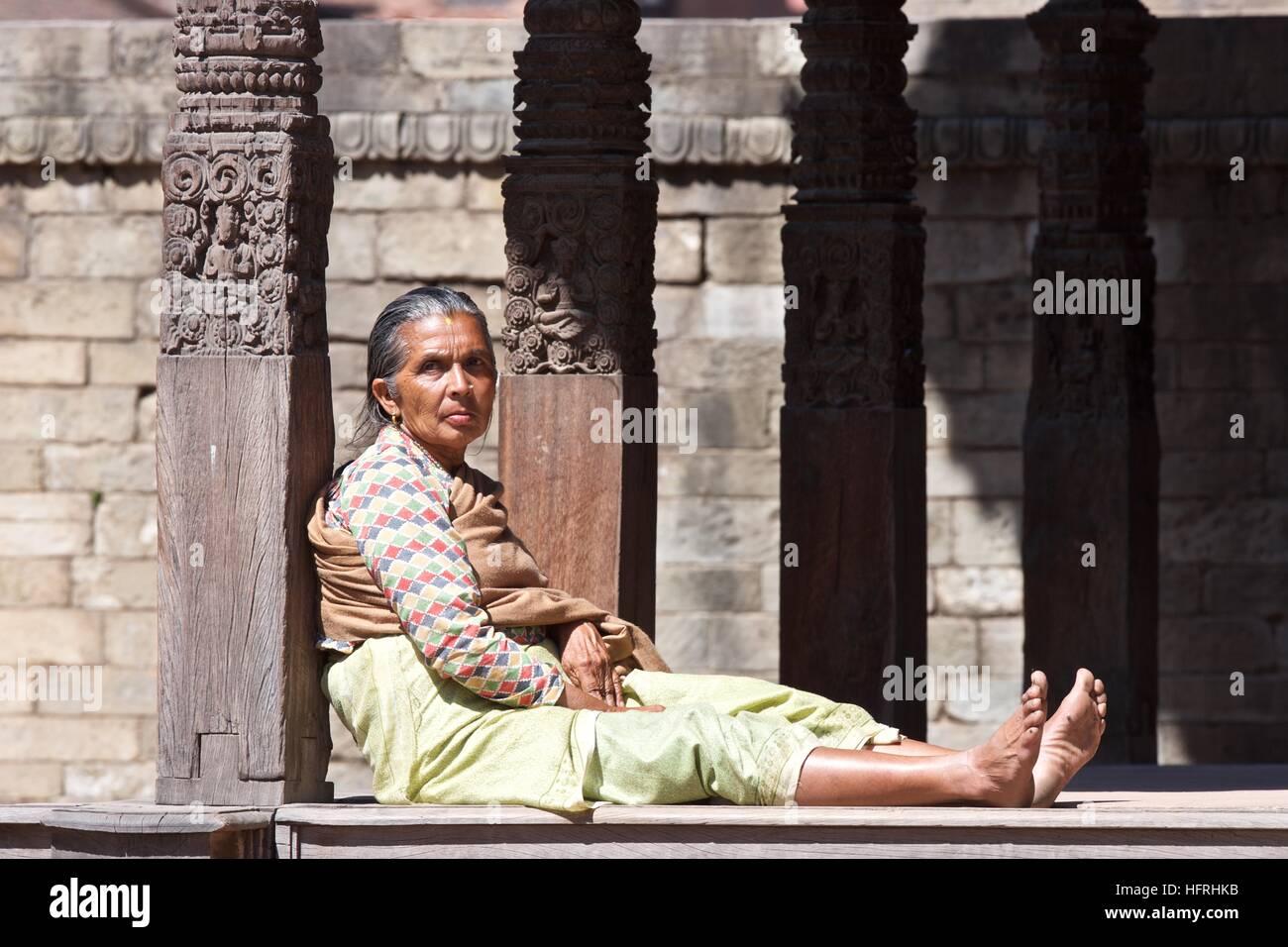Nepal Kathmandu Asia local woman lady street candid sitting wooden columns - Stock Image