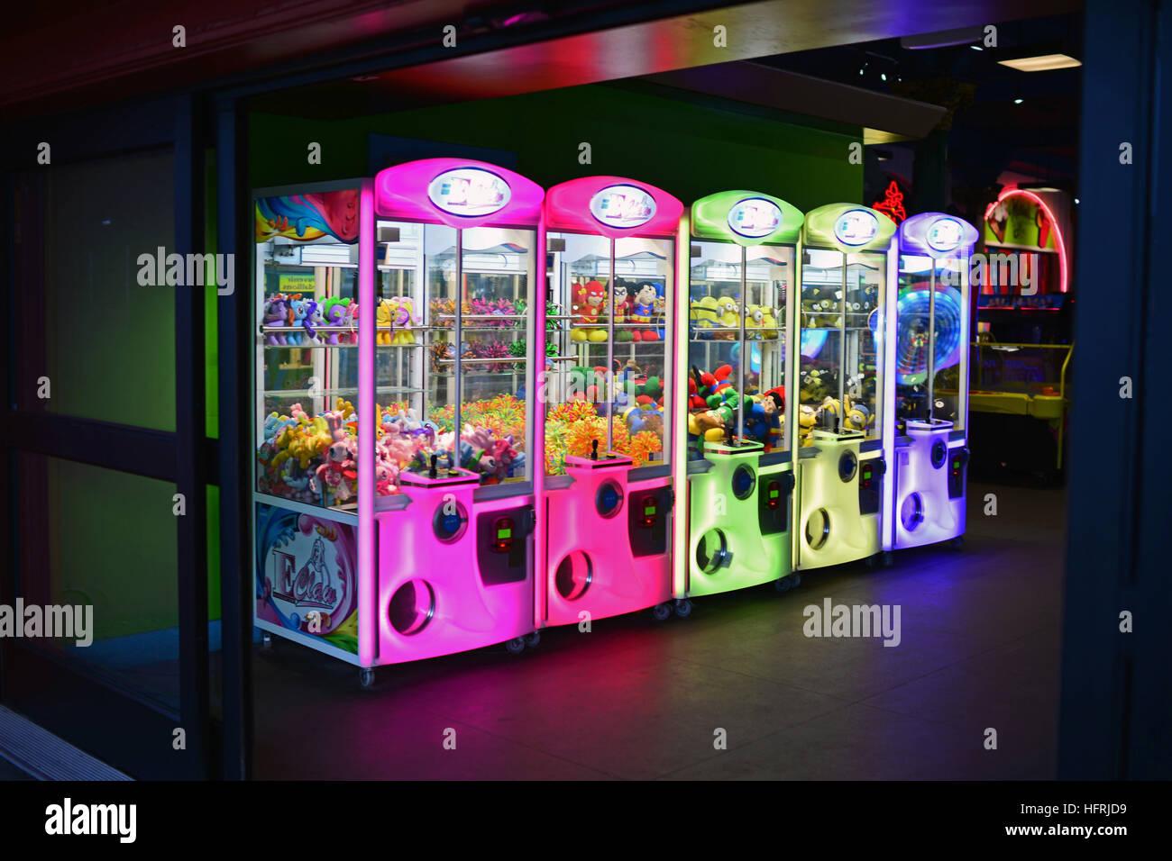 Claw machines in different neon colours, Santa Cruz, California. - Stock Image