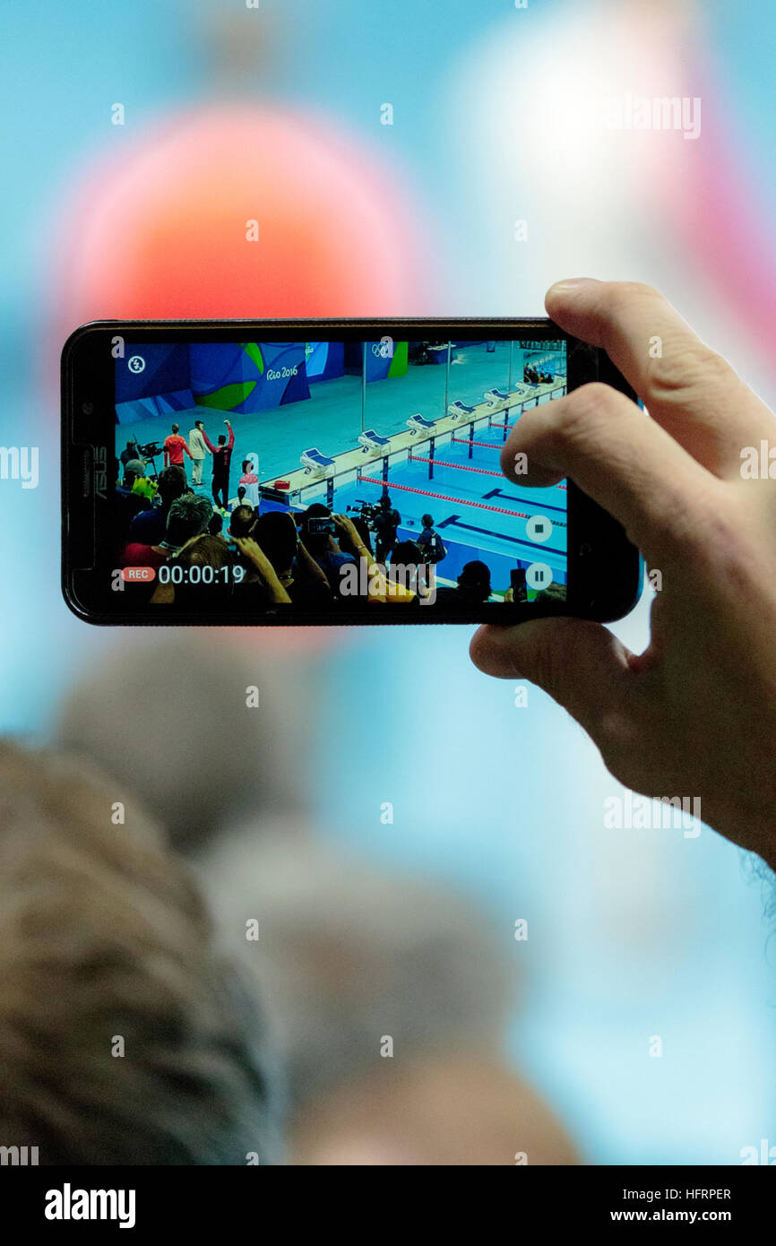 Rio de Janeiro, Brazil. 9 August 2016.   Spectator using mobile phone to photograph Michael Phelps (USA) the gold - Stock Image