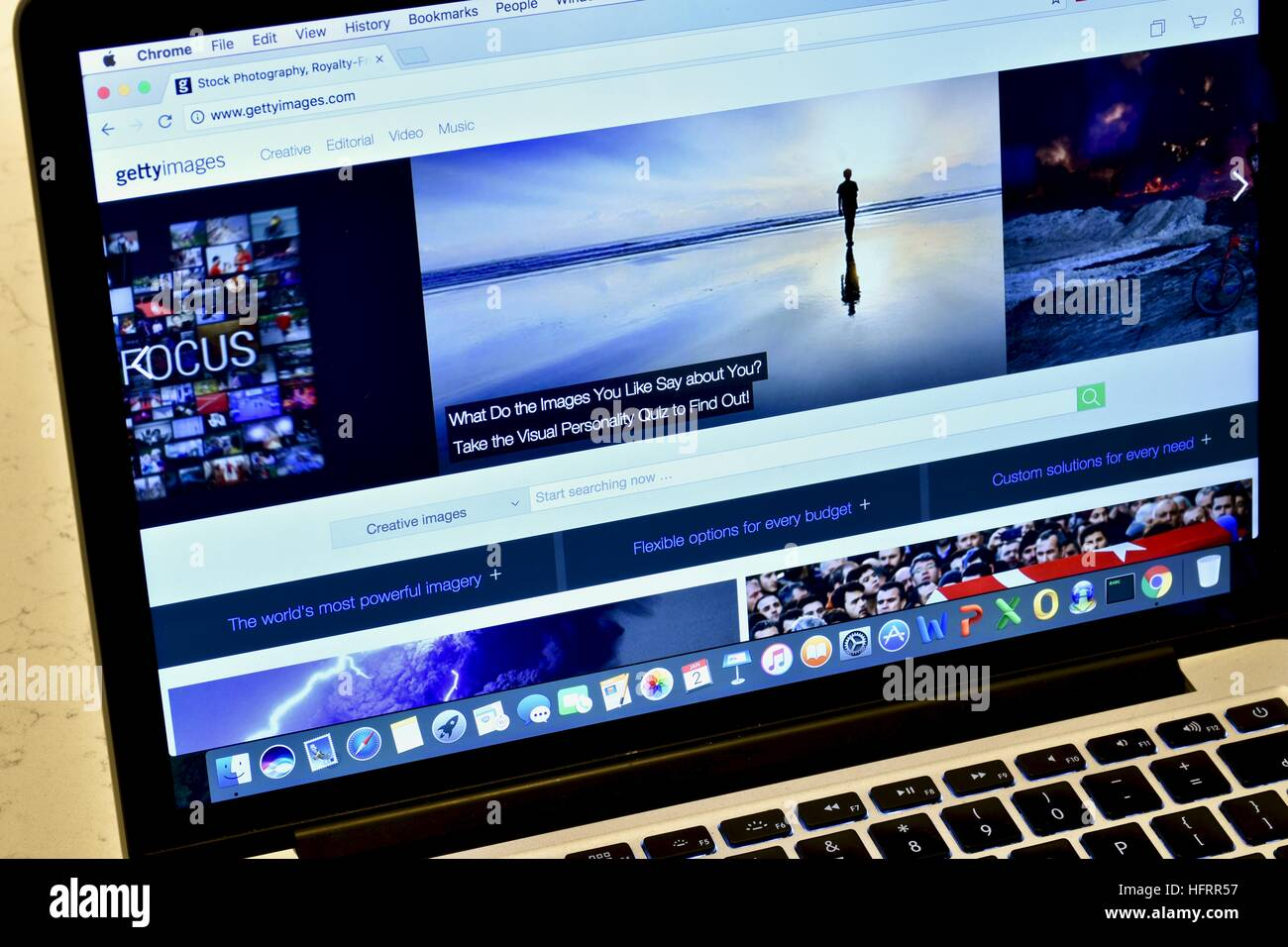 An Apple Macbook Pro displaying a stock photo website - Stock Image
