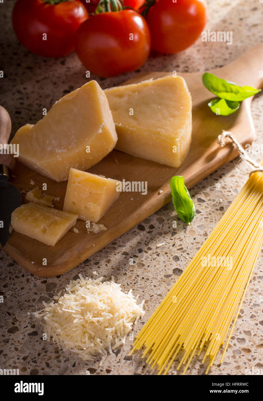 Blocks of Parmesan Cheese with Tomatoes, Basil Leaves, Pasta, and Grated Cheese - Stock Image