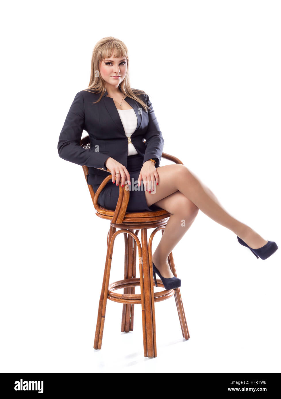Young beautiful business woman in a business suit, sitting on a bar stool. White isolated background. - Stock Image