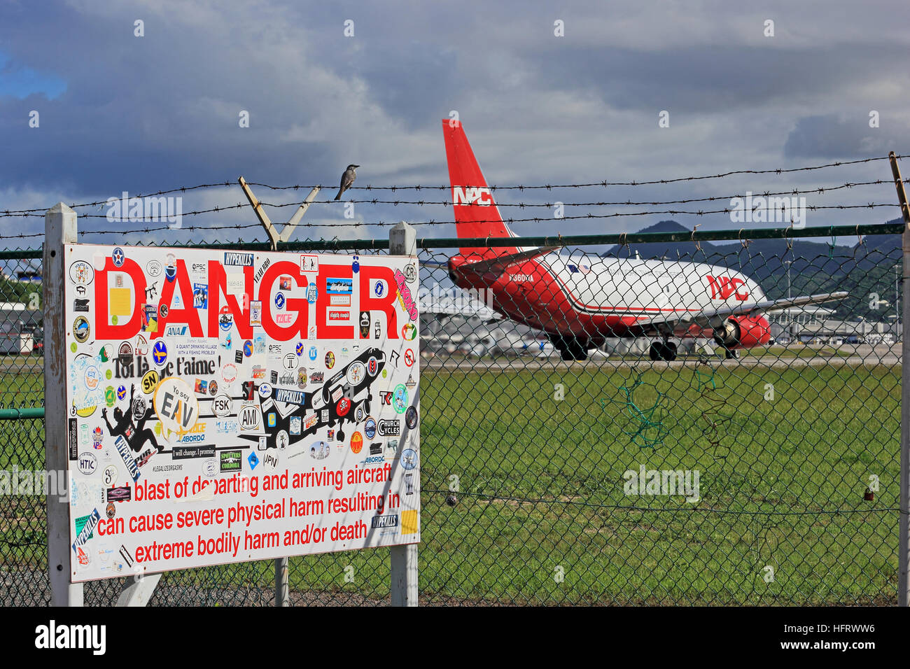 Warning sign on perimeter of airport, Maho beach, Philipsburg Airport, St Maarten, with Northern Air Cargo Boeing - Stock Image