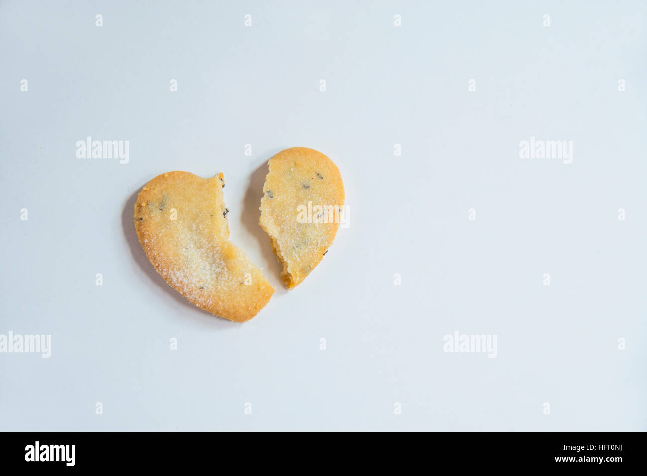 Heart-shaped biscuit, broken in two pieces. - Stock Image