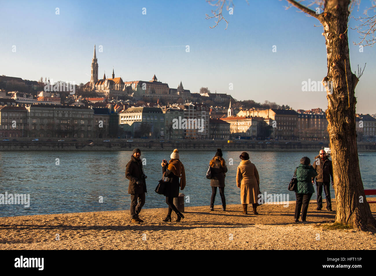 Tourists enjoying the winter sun  and the panorama to the Buda Castle near the danube river, in Budapest. Stock Photo