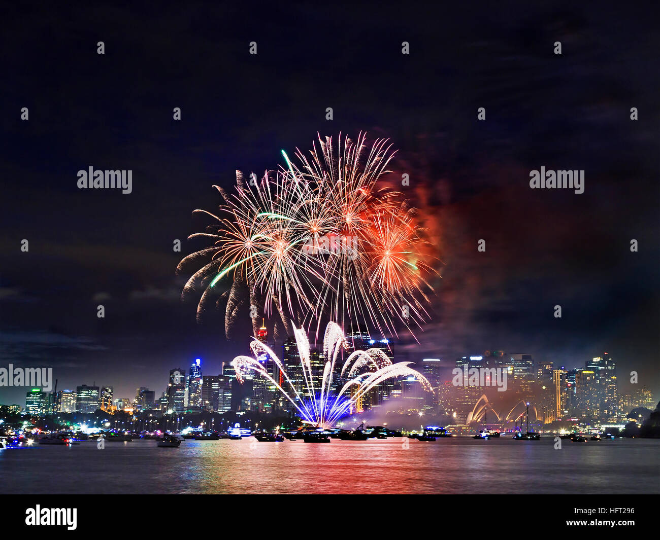 Bright red balls of fireworks in Sydney during New Year eve celebration across Harbour over city CBD towers and - Stock Image