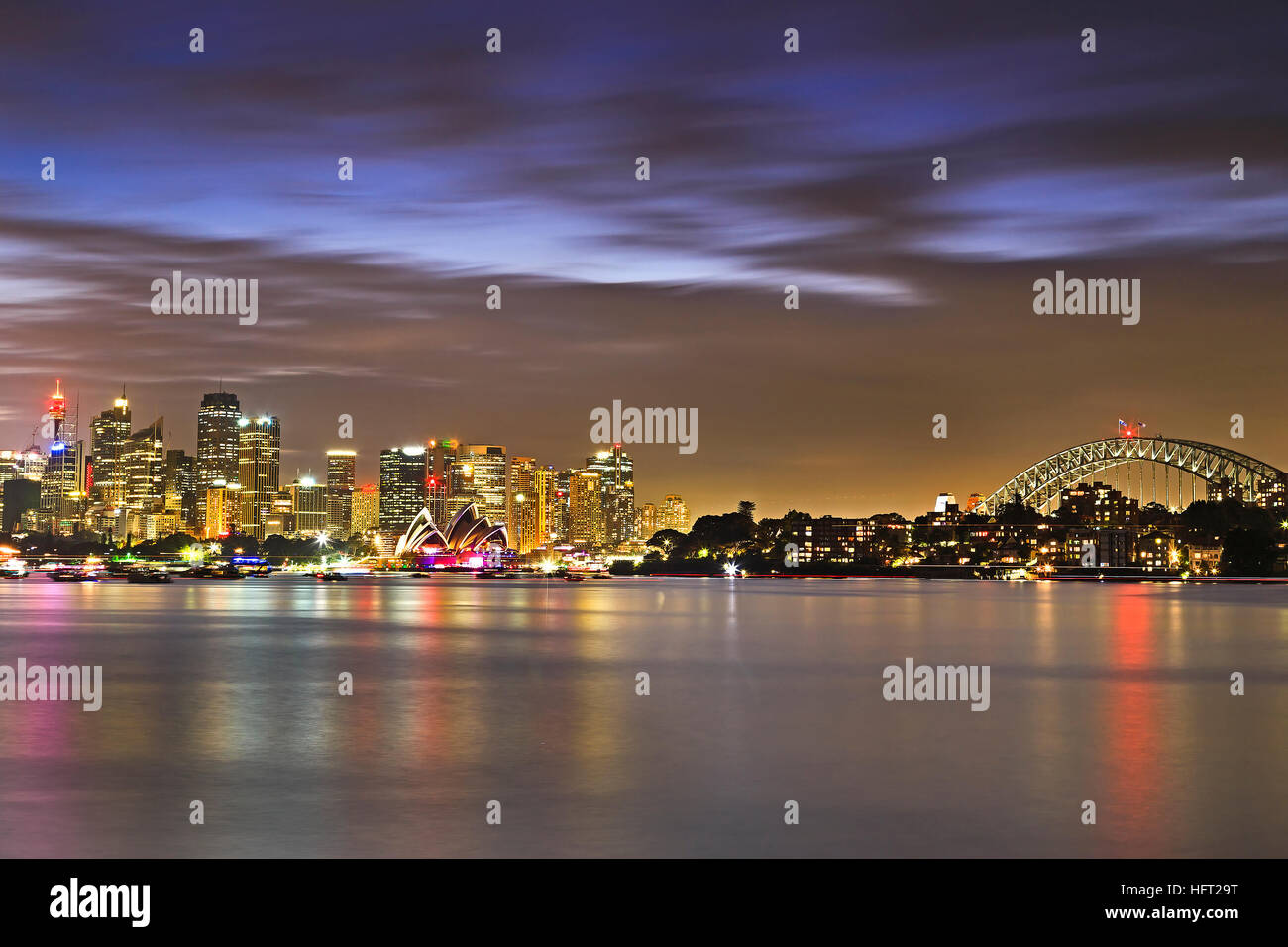 Panorama of SYdney city landmarks over Harbour from Bridge to Skysrapers and towers of CBD at sunset. - Stock Image