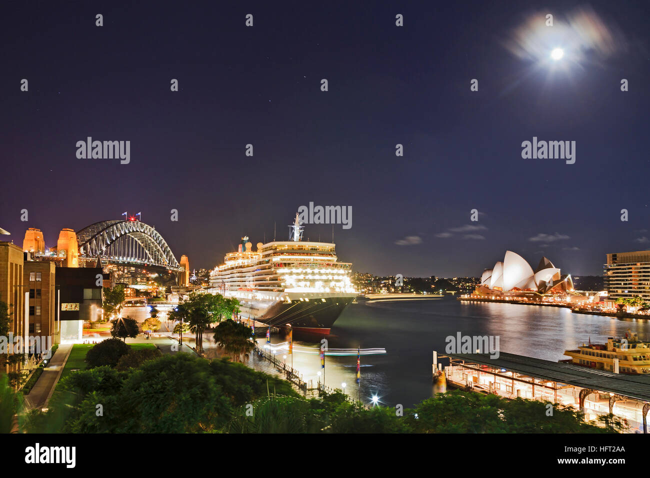 Dark sunset time with full moon above Sydney Harbour, Bridge, overseas passenger terminal and circular quay ferries - Stock Image