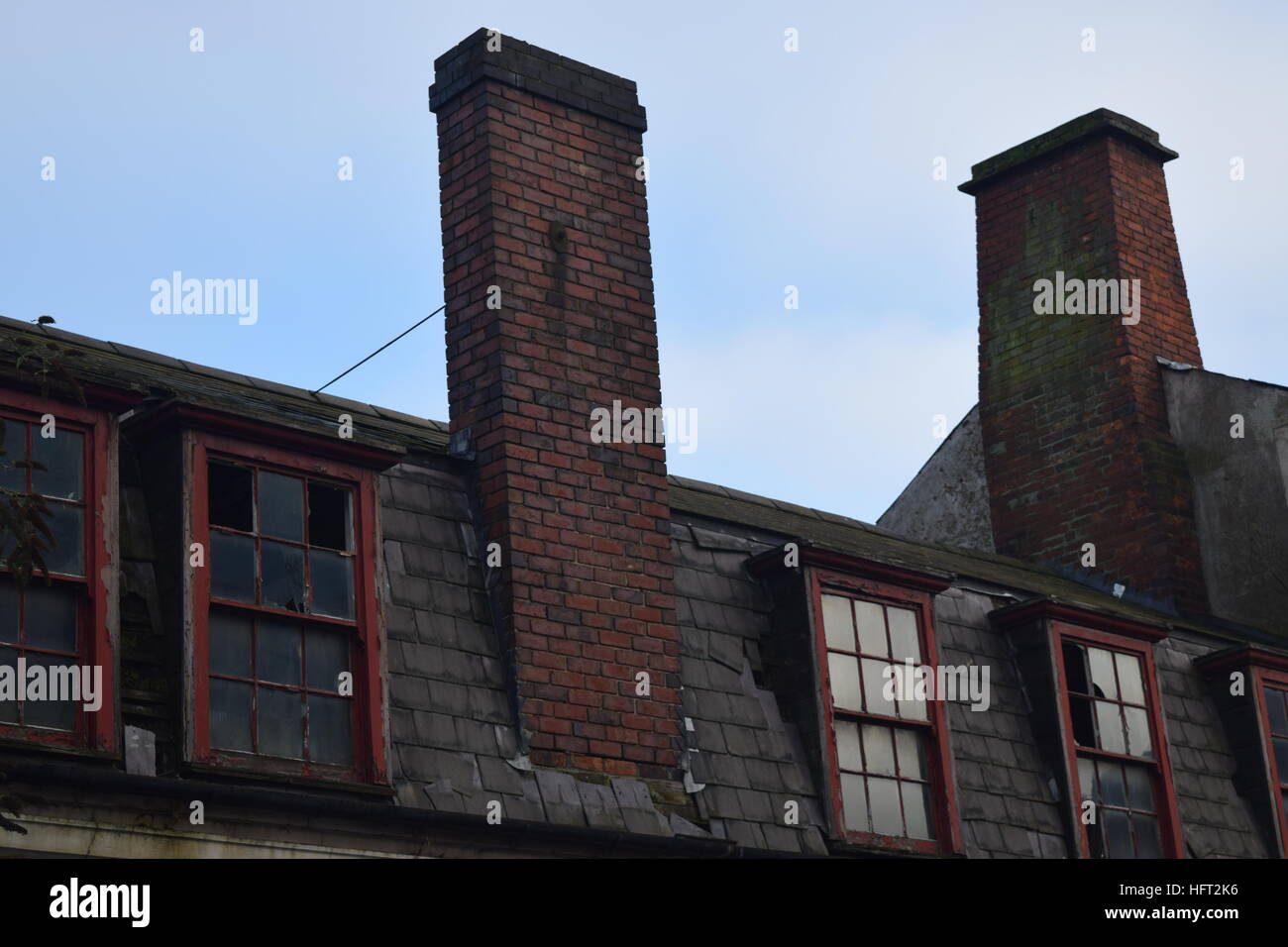 Decayed first floor windows and chimneys on a Grade II listed Stock