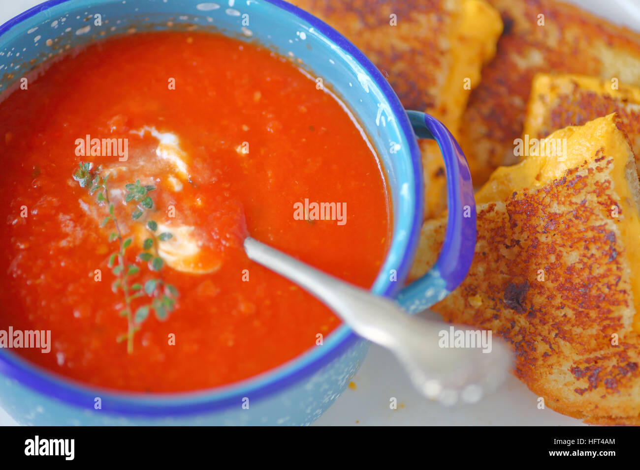 Tomato soup in an enamelware bowl with a grilled cheese sandwich cut in triangles - Stock Image