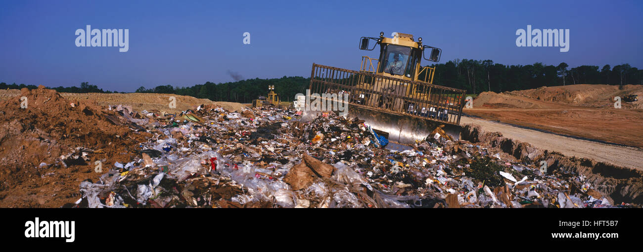 Heavy equipment at work in a sanitary landfill operation. - Stock Image